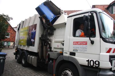 Bild: Ein Papierbehälter wird in ein Entsorgungsfahrzeug gekippt.