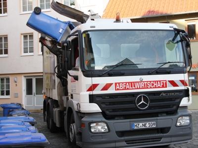 Bild: Ein Fahrzeug der Nordharz Entsorgung GmbH entleert einen Altpapierbehälter der enwi.